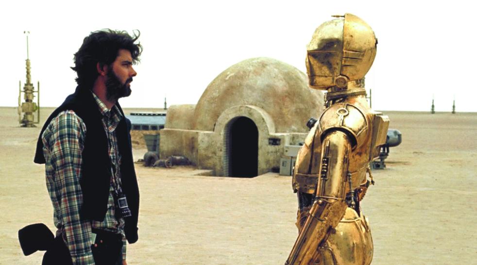Лукас на съемочной площадке Звездных Войн рядом с роботом.