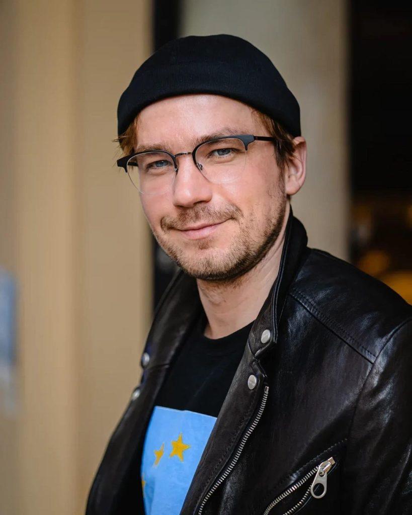 Российский киноактер Александр Петров в черной шапочке.
