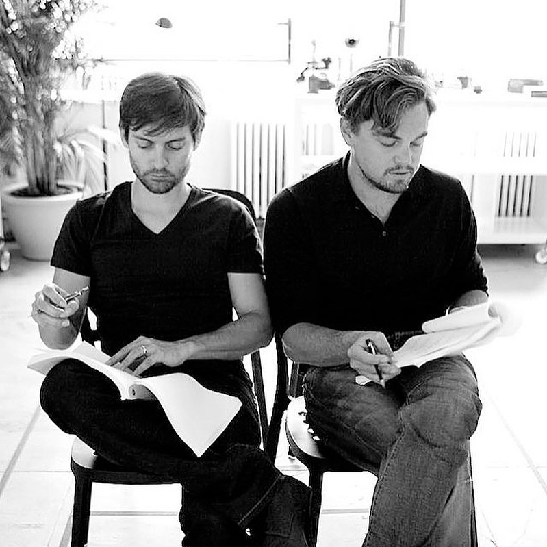 Актер Тоби Магуайр и Леонардо Ди Каприо учат сценарий сидя на стульях.