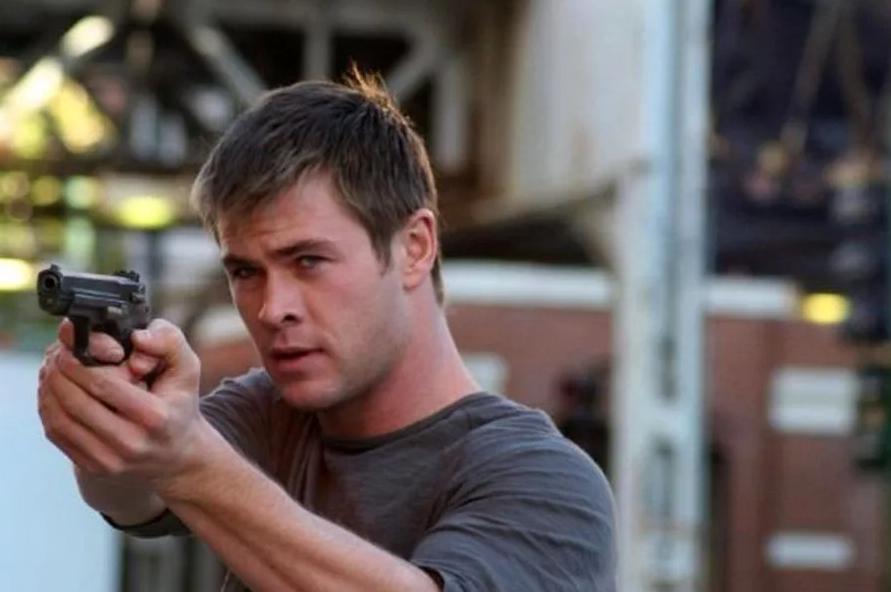 Киноактер Крис Хемсворт с пистолетом в фильме.