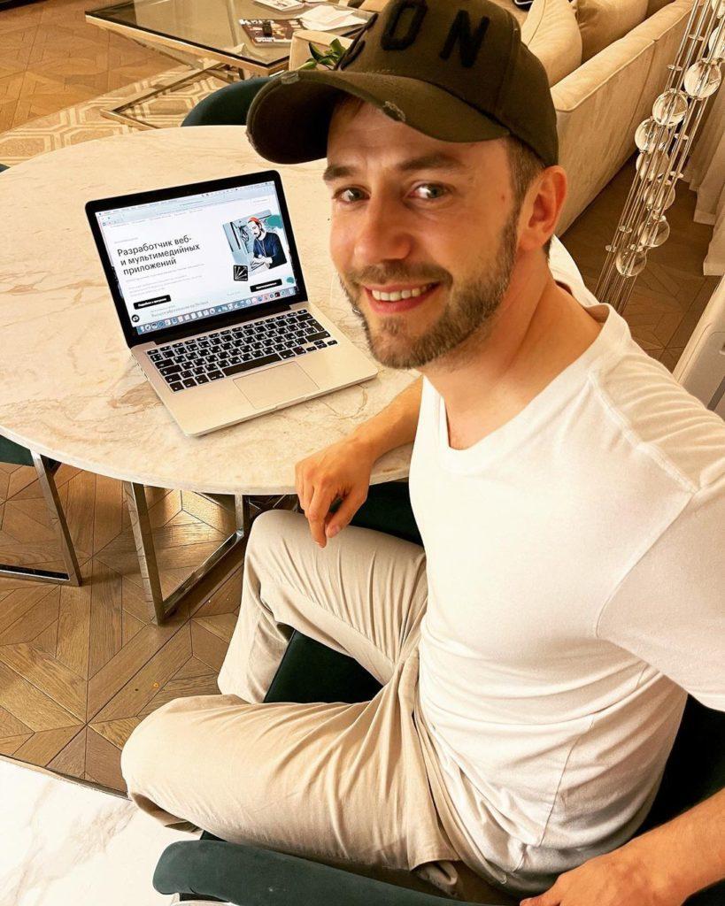 Актер Иван Жидков в кепке с ноутбуком.