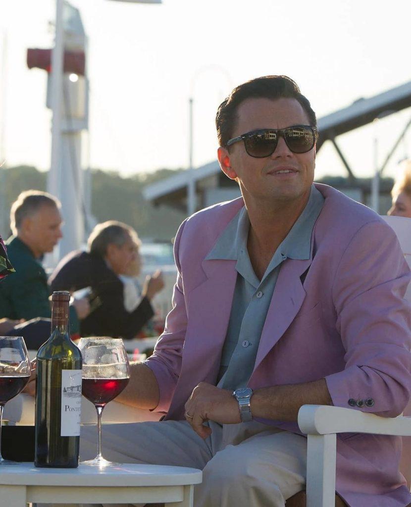 актер Леонардо Ди Каприо (Leonardo DiCaprio) в розовом пиджаке и с стакан красного вина на столе.