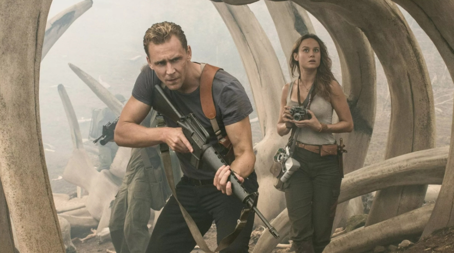 актер Том Хиддлстон с автоматом. Рядом девушка с фотоапаратом.