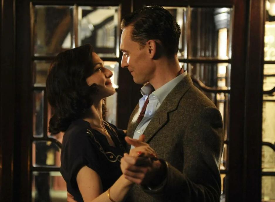 актер Том Хиддлстон танцует с девушкой.