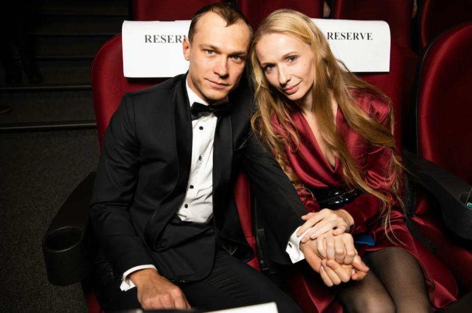 Киноактер Юрий Борисов вместе с женой. Смокинг и вечернее платья. Сидят за руку.