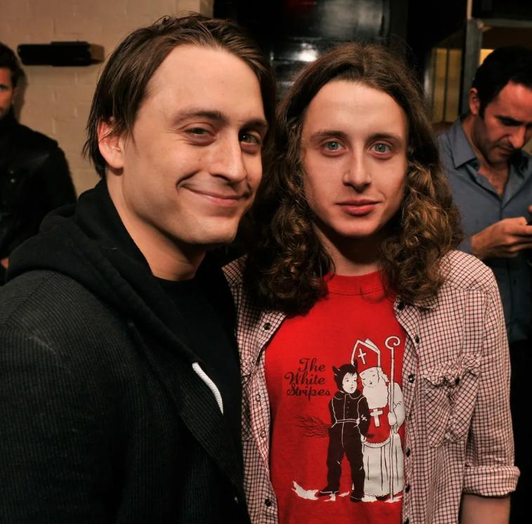 актер Киран Калкин и его брат Рори с длинными волосами и в красной футболке.