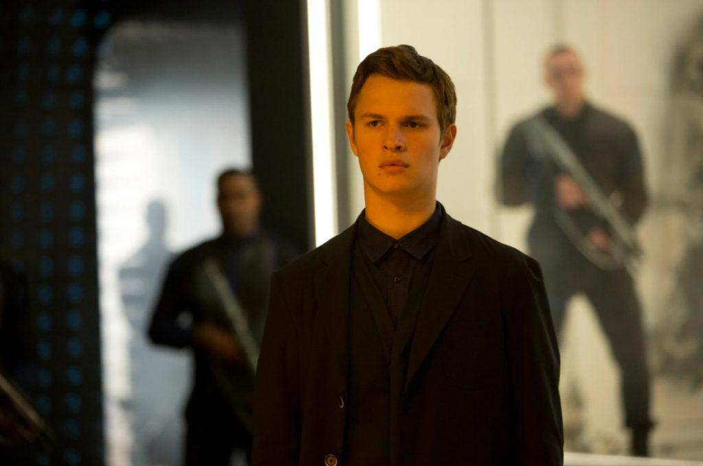 Актер и певец Энсел Эльгорт в фильме Дивергент стоит в черном пиджаке.