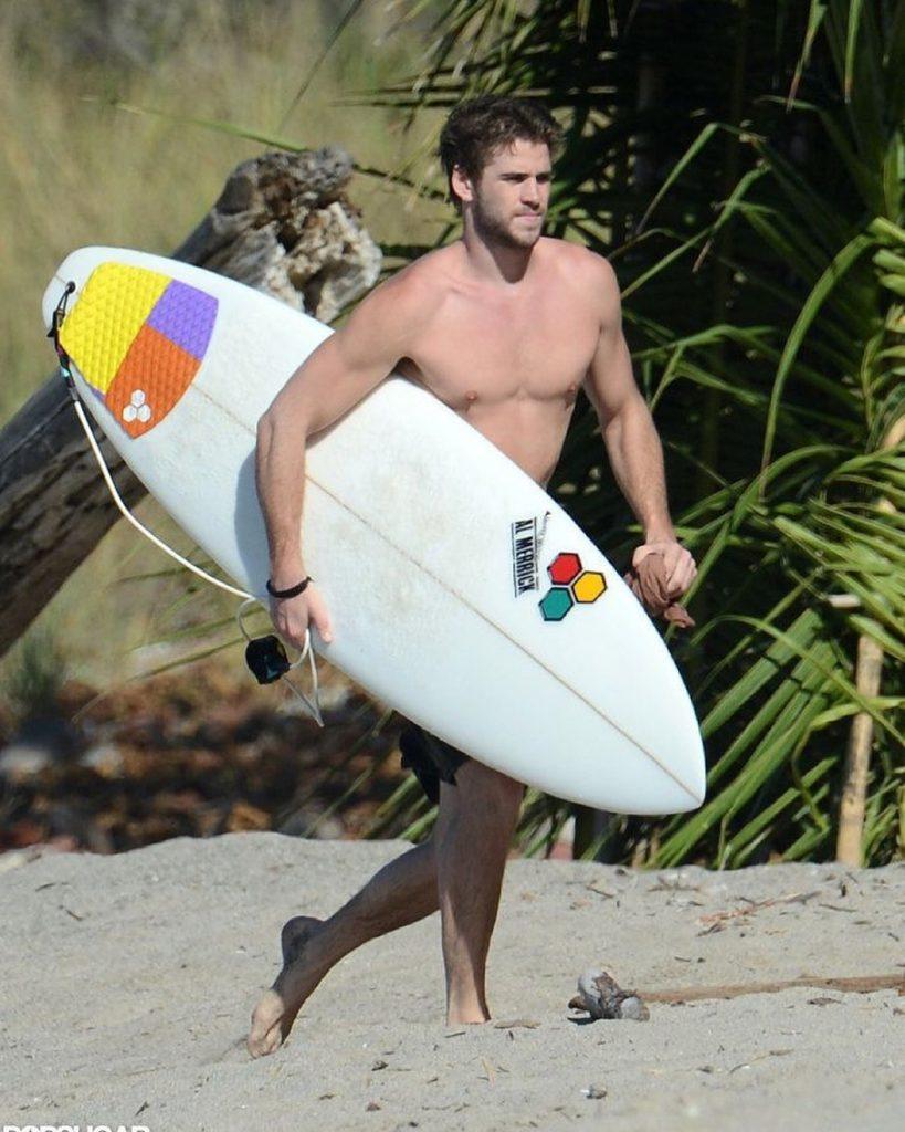 Киноактер Лиам Хемсворт с доской для сёрфа бежит по пляжу.