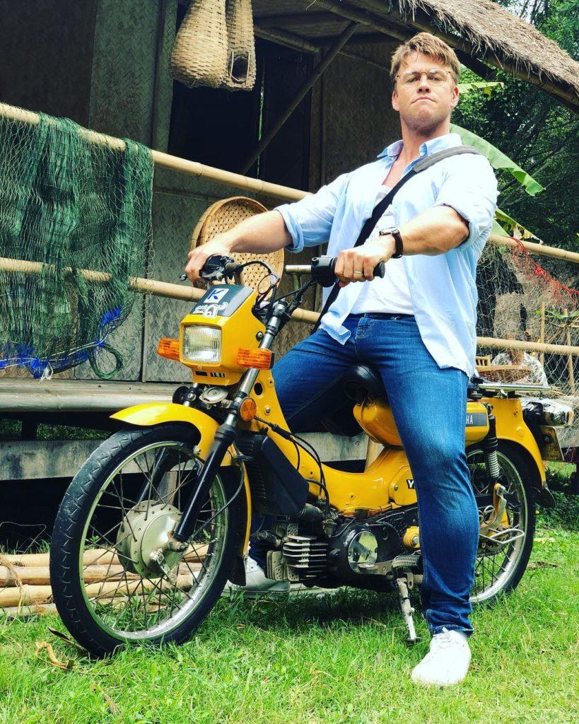Австралийский актер Люк Хемсворт на желтом мотоцикле.