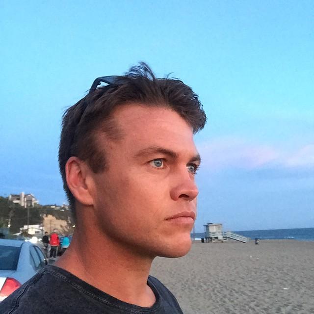 Австралийский актер Люк Хемсворт на пляже.