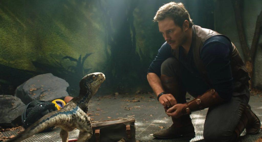 Актер Крис Прэтт (Chris Pratt) в роли Оуэна Грейди разговаривает с маленьким динозавром.