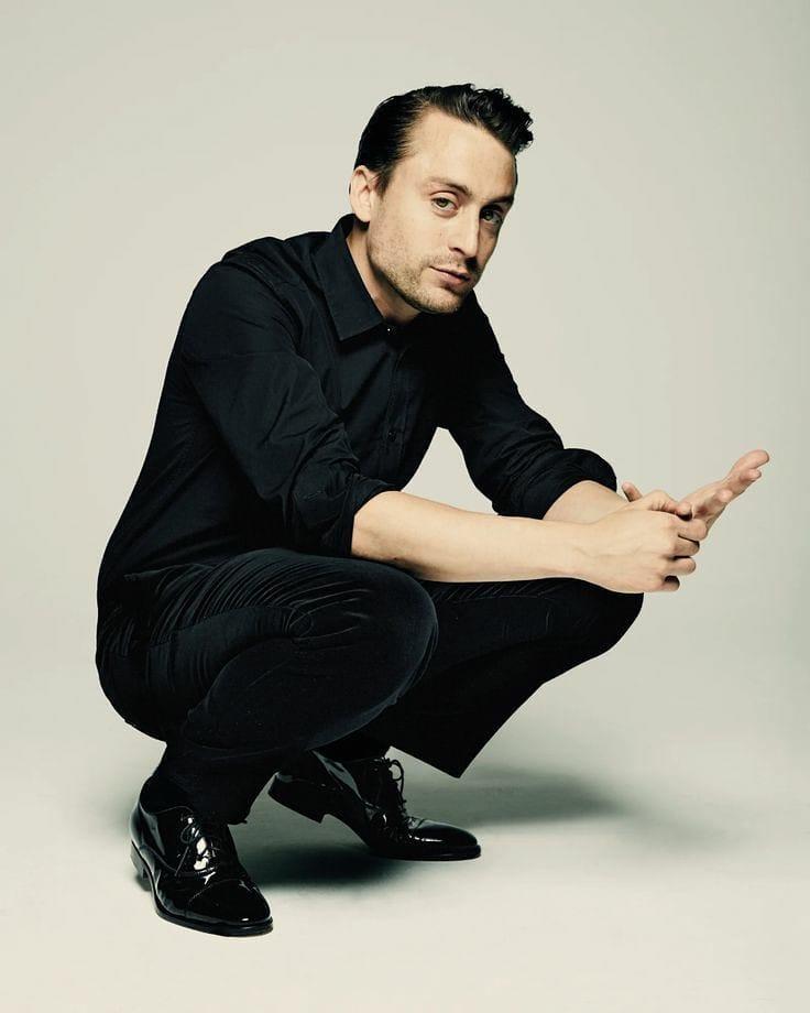 Актер Киран Калкин в черной рубашке и брюках сидит на корточках.