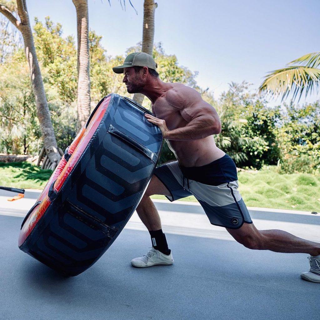 Киноактер Крис Хемсворт поднимает огромное колесо с голым торсом и в шортах. Огромные мускулы Криса Хемсворта.
