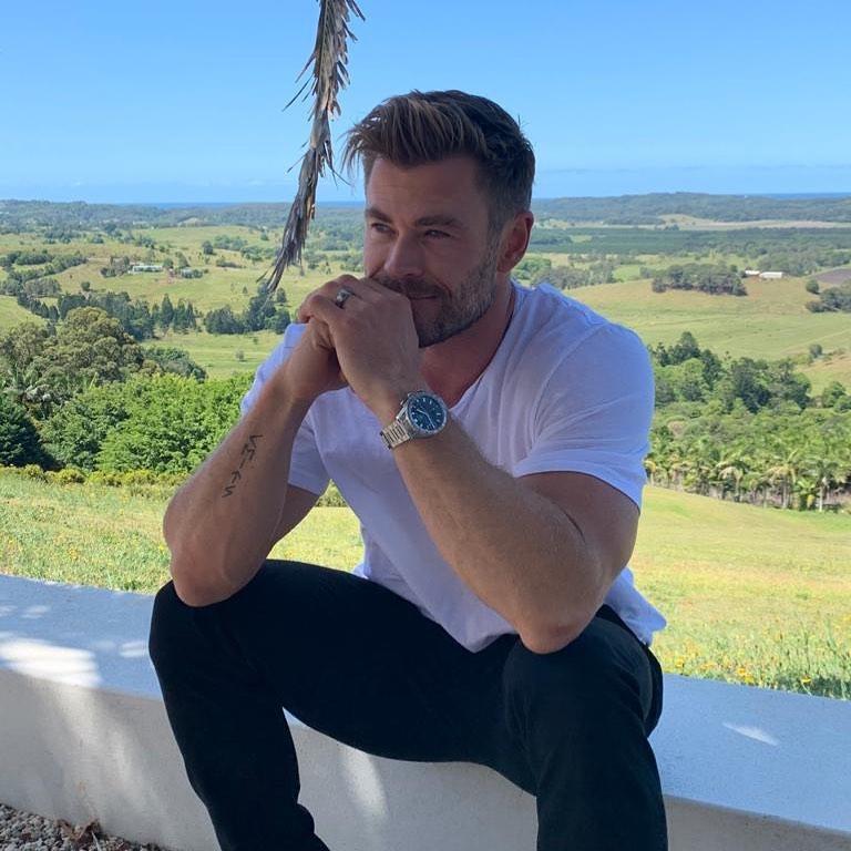 Киноактер Крис Хемсворт сидит на фоне природы Австралии.
