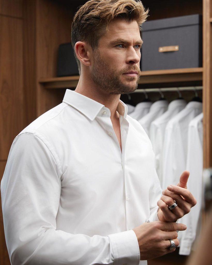 Киноактер Крис Хемсворт в белой рубашке.
