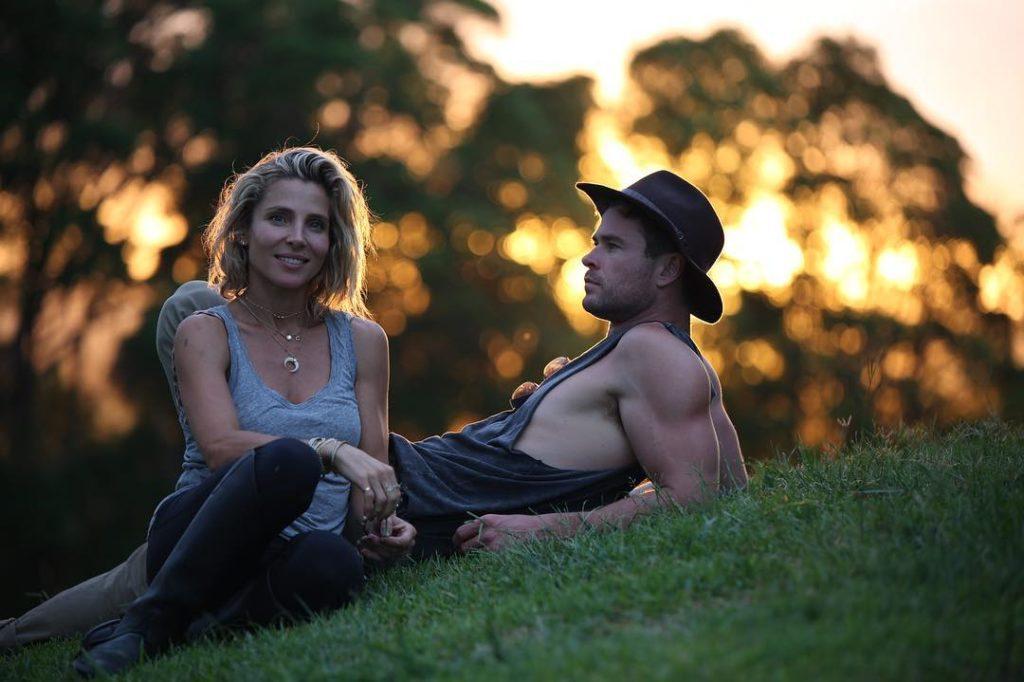 Киноактер Крис Хемсворт и его жена Эльза Патаки лежат на зеленой траве при закате.