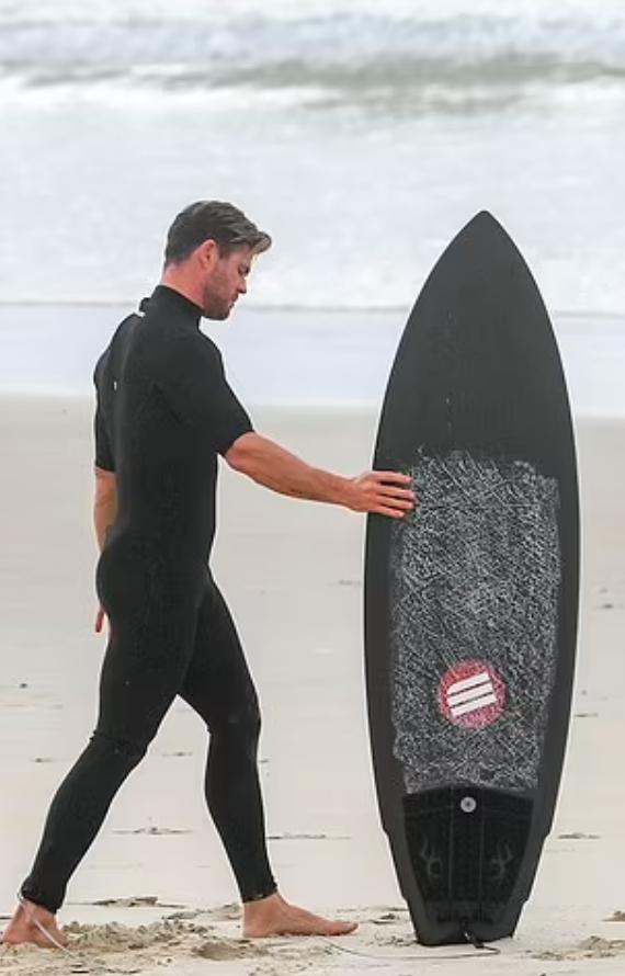 Киноактер Крис Хемсворт смотрит на доску для серфинга в плавательном черном костюме.