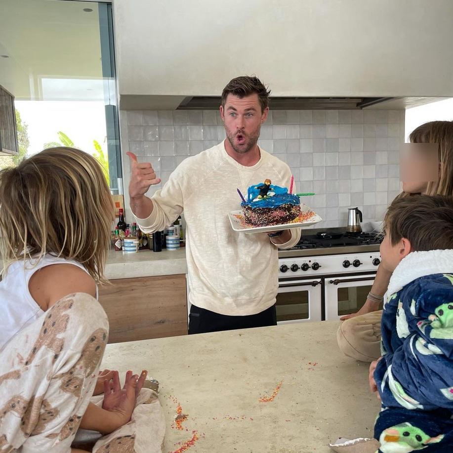 Киноактер Крис Хемсворт с детьми и тортом на свой день рождения.