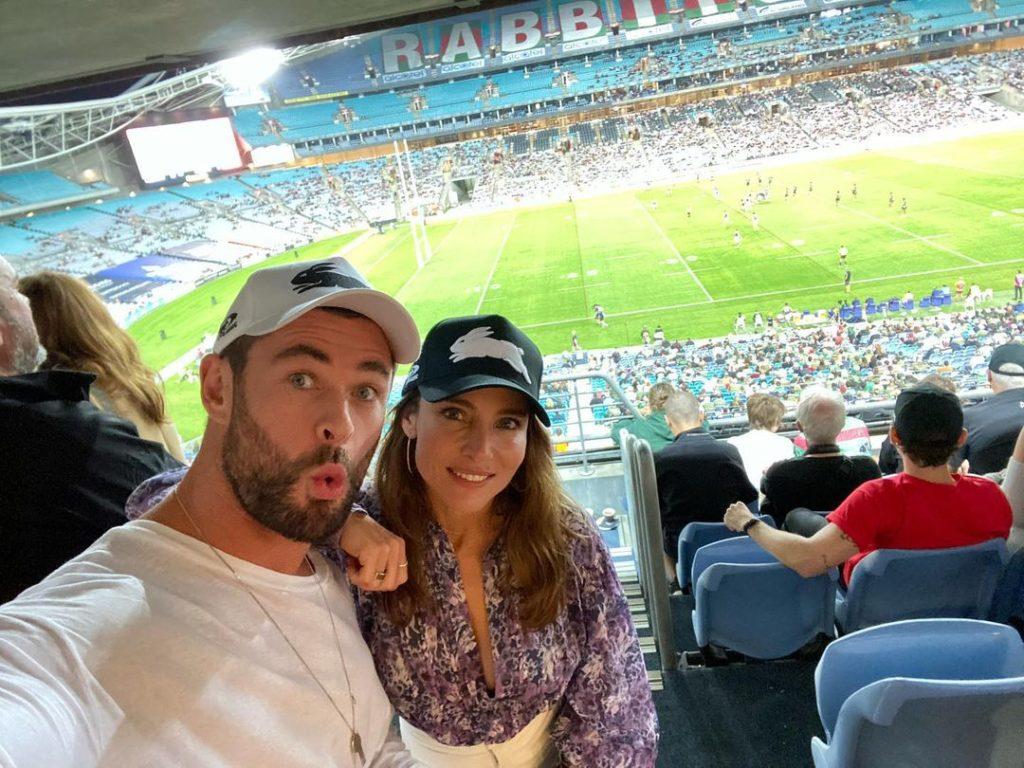 Киноактер Крис Хемсворт на футбольном матче вместе с женой в кепках.