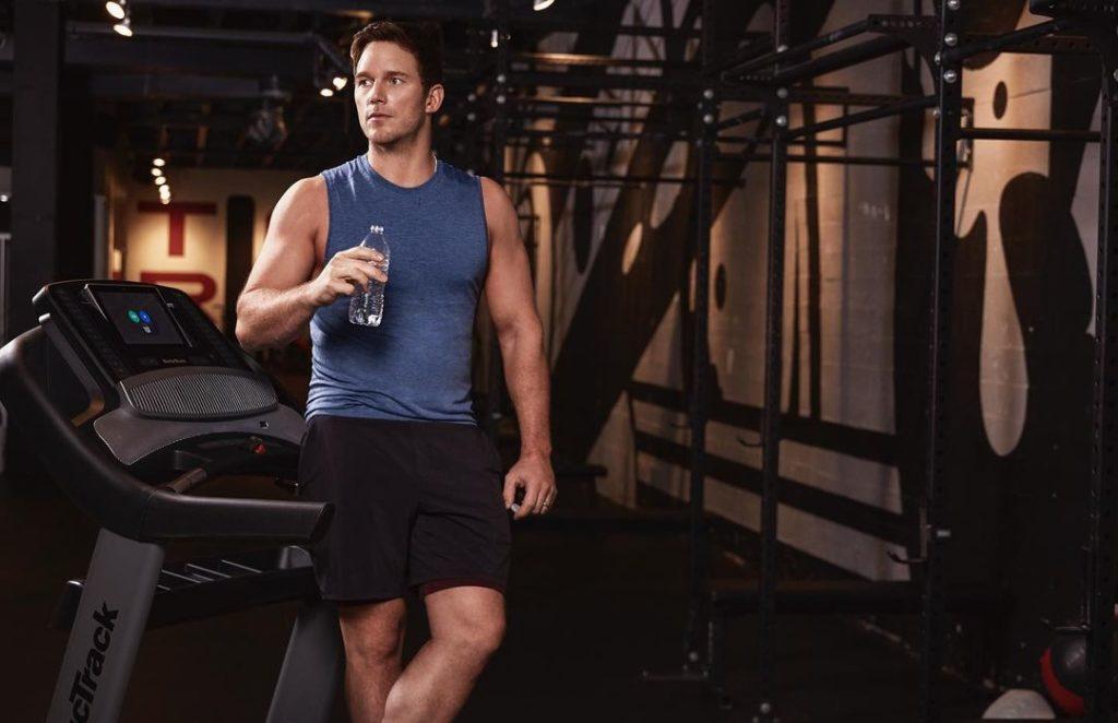 Актер Крис Прэт с бутылкой воды и в футболке в спортзале.