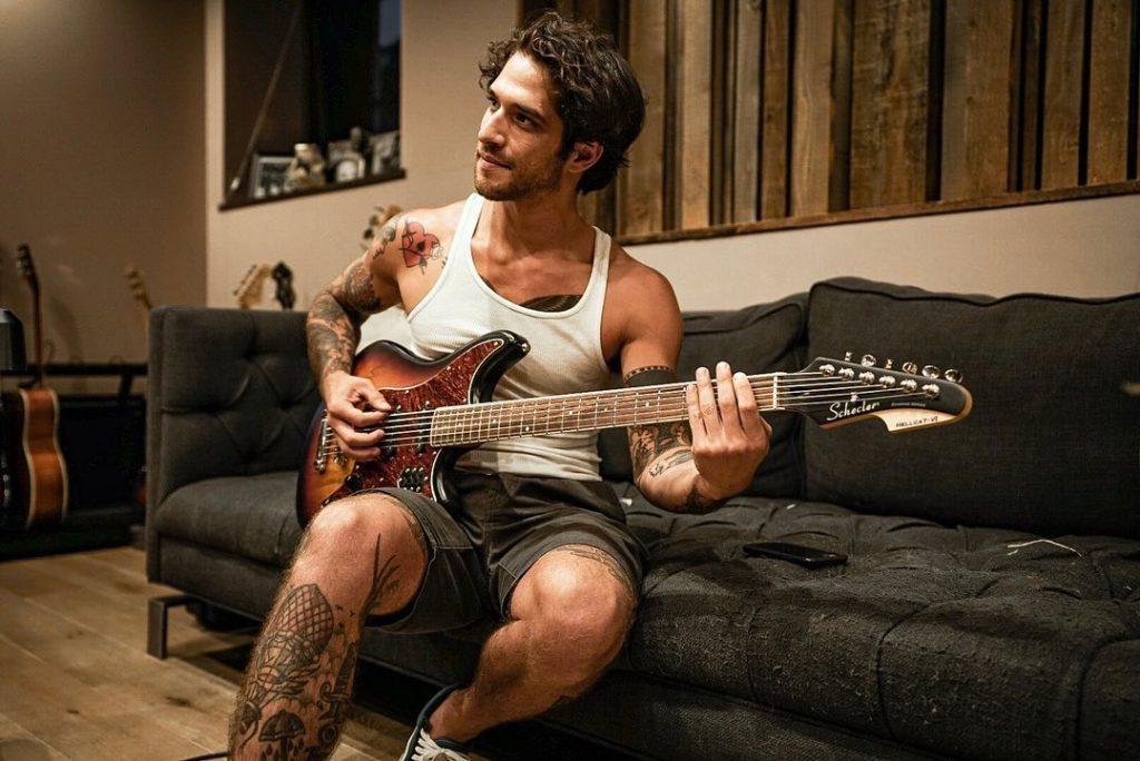 Тайлер Пози с гитарой сидит на диване.
