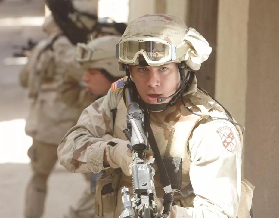 Актер Ченнинг Татум в роли морского пехотинца с автоматом.