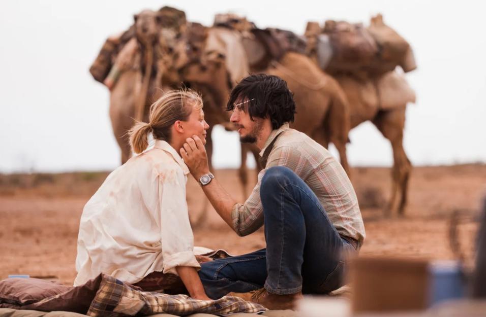 Актер Адам Драйвер в пустыня сидит и смотрит на девушку.
