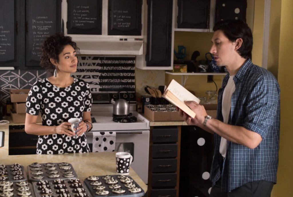 Актер Адам Драйвер читает книгу на кухне вместе с девушкой.