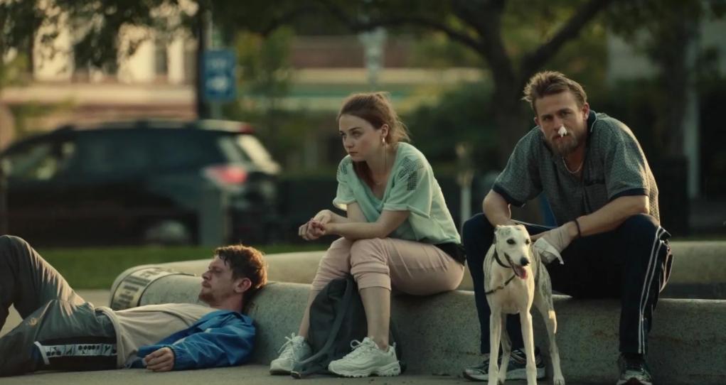 Актер Чарли Ханнэм сидит на тратуаре.