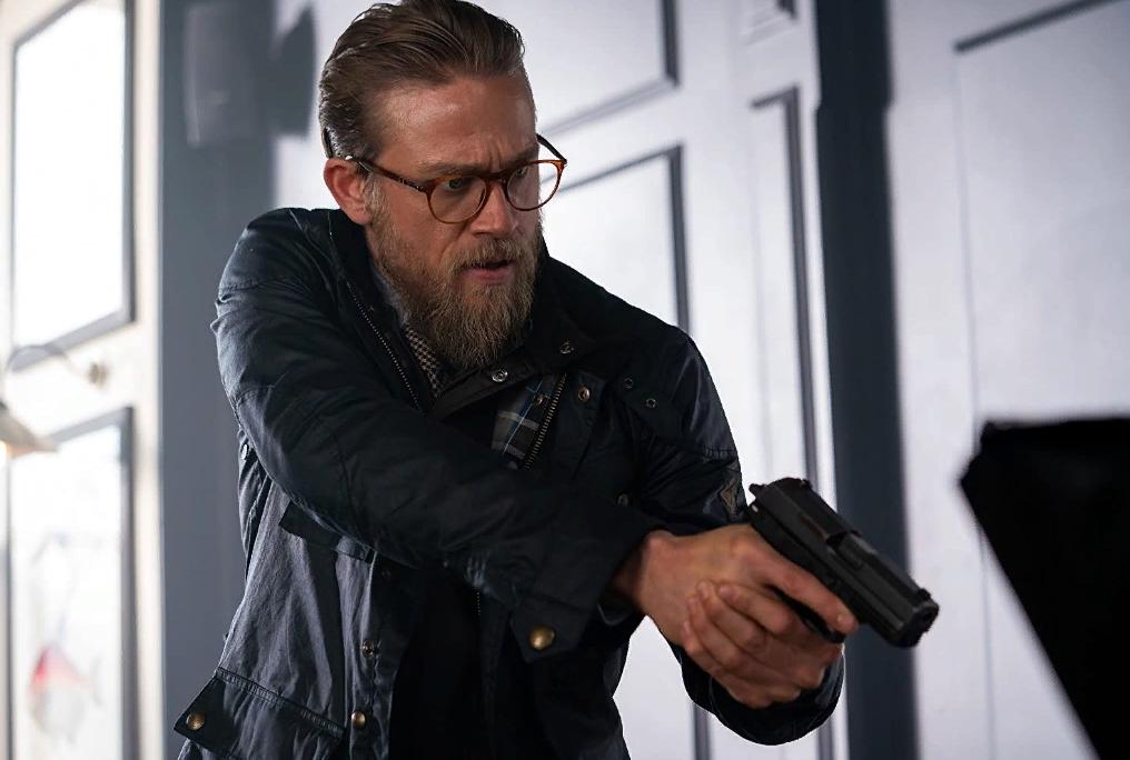 Актер Чарли Ханнэм в очках и с пистолетом. Кадр из фильма.