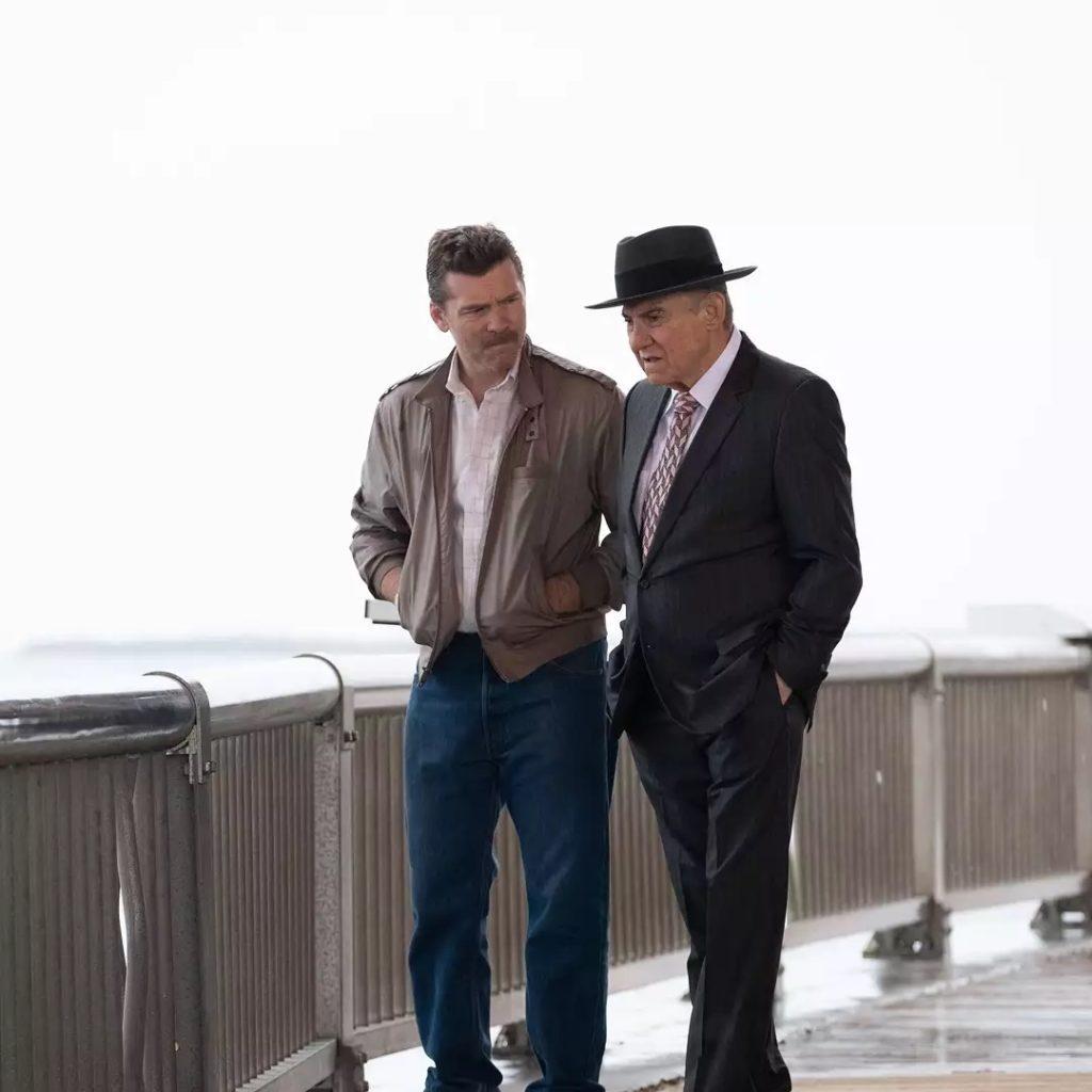 Актер Сэм Уортингтон и Харви Кейтель в шляпе разговаривают на набережной.