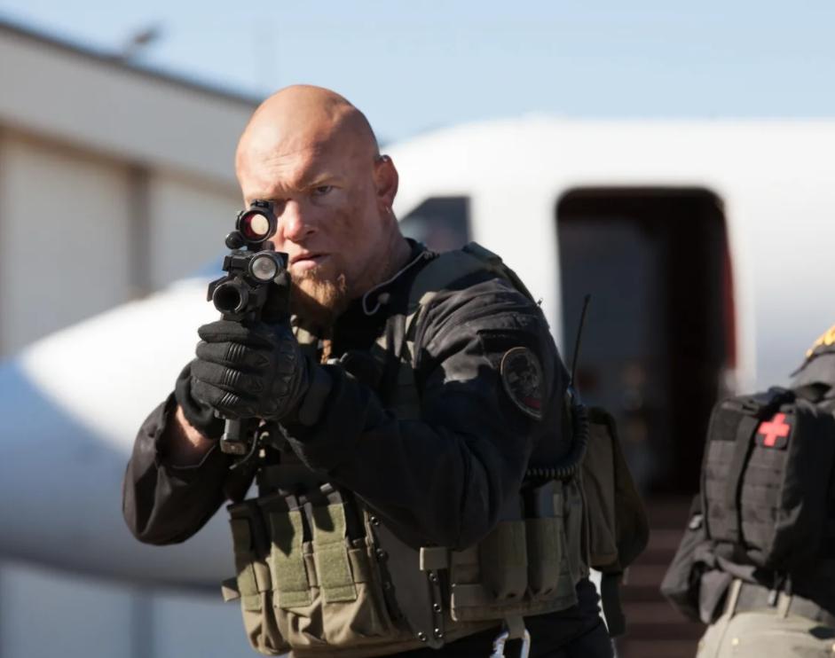 Актер Сэм Уортингтон в фильме Саботаж смотрит в прицел автомата.