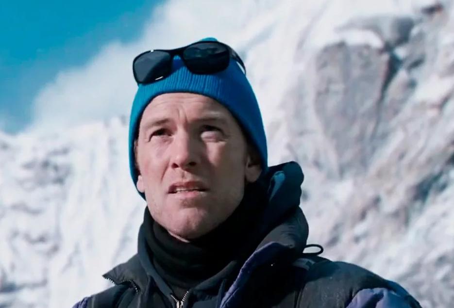 Актер Сэм Уортингтон на фоне гор в зимней одежде.