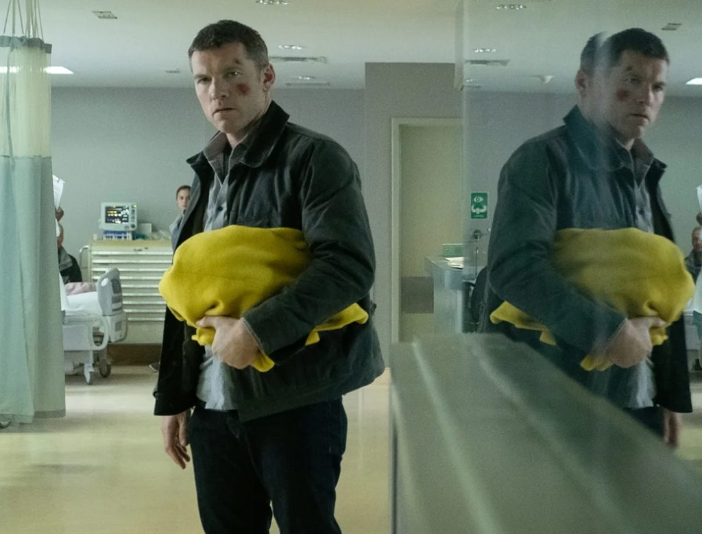 Актер Сэм Уортингтон с желтой одеждой в руках.