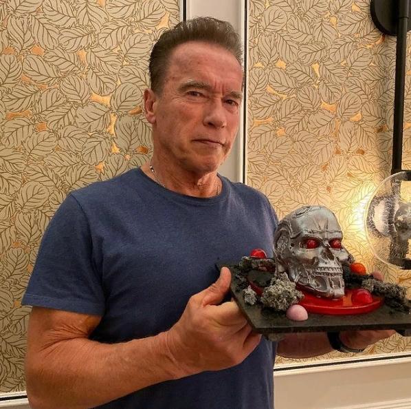 Арнольд Шварценеггер в старости стоит с черепом терминатора.