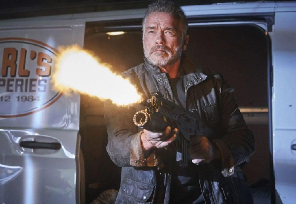 Арнольд Шварценеггер стреляет из автомата.