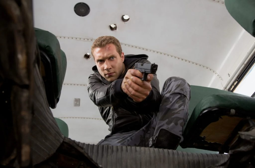 Джай Кортни кортни с пистолетом в роли Кайла Риза.