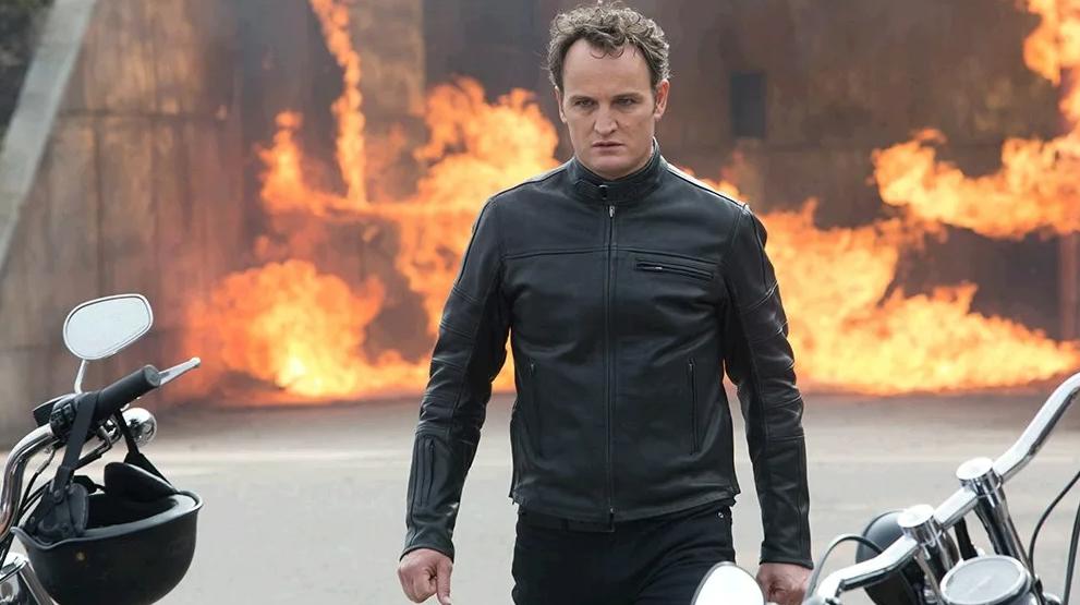Джейсон Кларк как Терминатор идет на фоне огня.