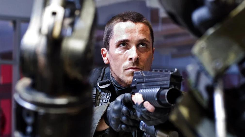 Кристиан Бейл с пистолетом, в роли Джона Коннора.