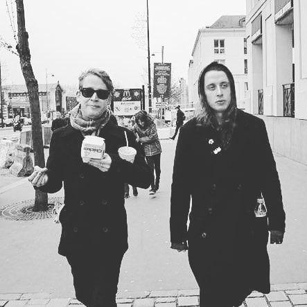 Маколей Калкин и его брат Рори идут по улице.