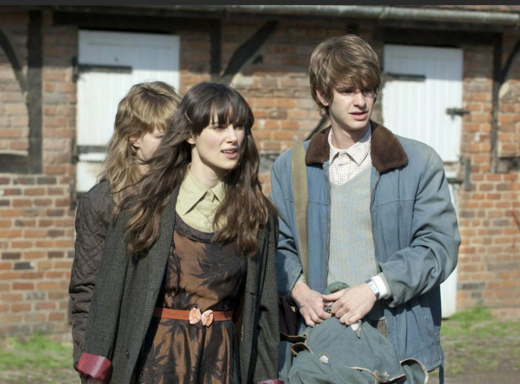 Актер Эндрю Гарфилд в роли Томми. Стоит рядом с девушками.
