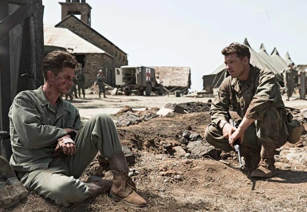 Актер Эндрю Гарфилд сидит на земле. В роли Десмонда Досса. Рядом Сэм Уортингтон в роли капитана Гловера.