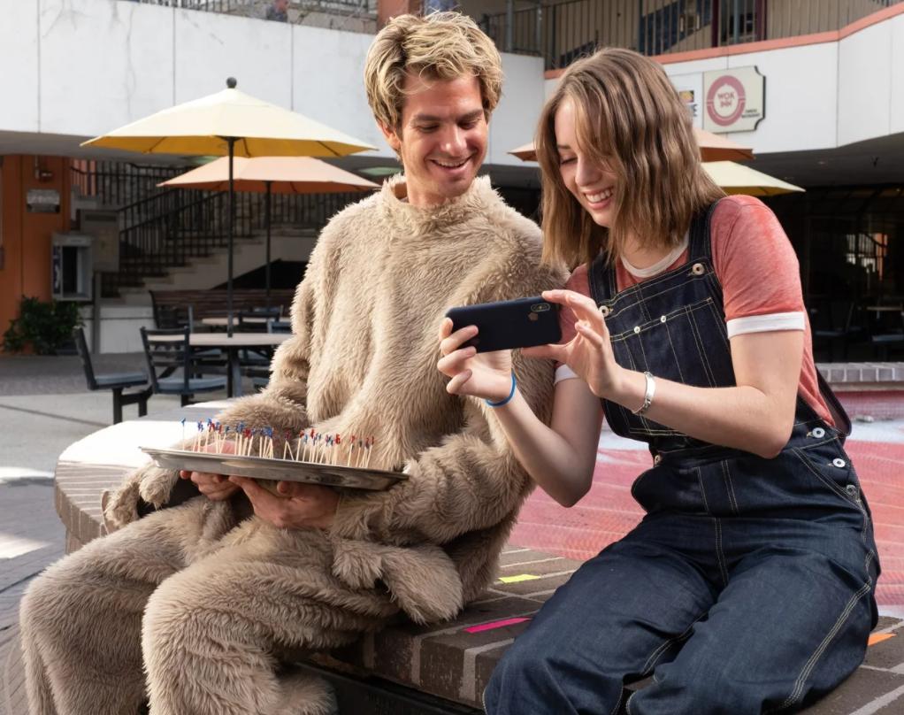 Актер Эндрю Гарфилд и девушка смотрят в смартфон.
