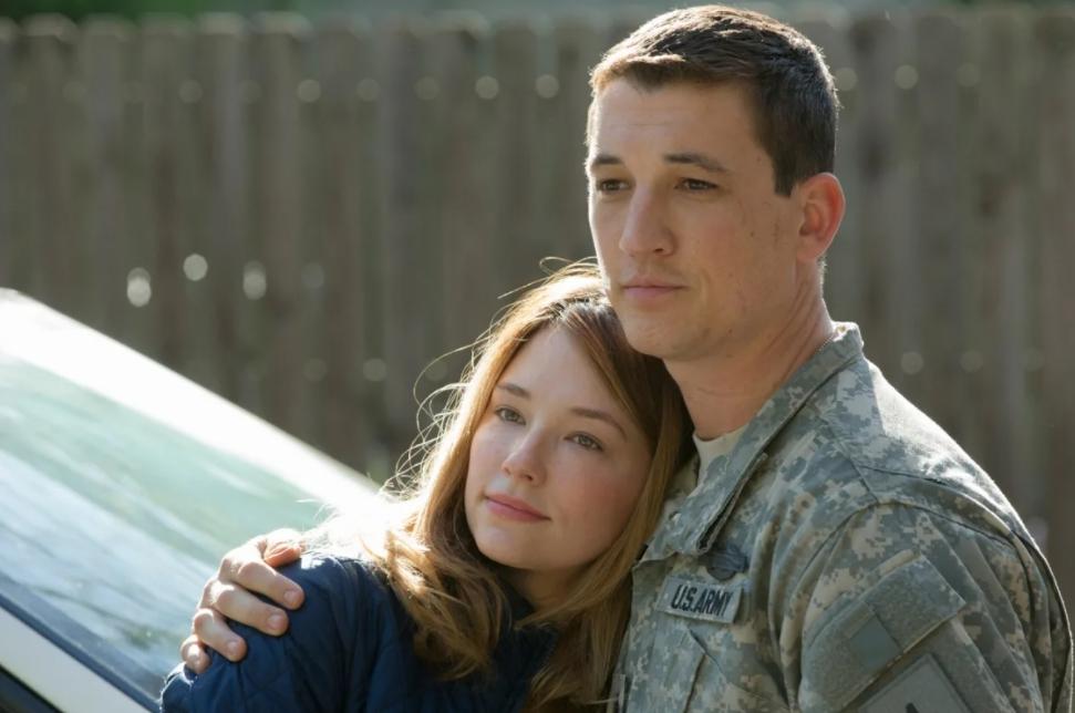 Киноактер Майлз Теллер в военной форме обнимает девушку.